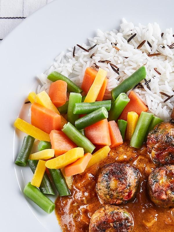 Ein weißer Teller mit den LÄTTLAGAT Gemüsebällchen mit Reis, grünen Bohnen, Karotten und Currysoße.