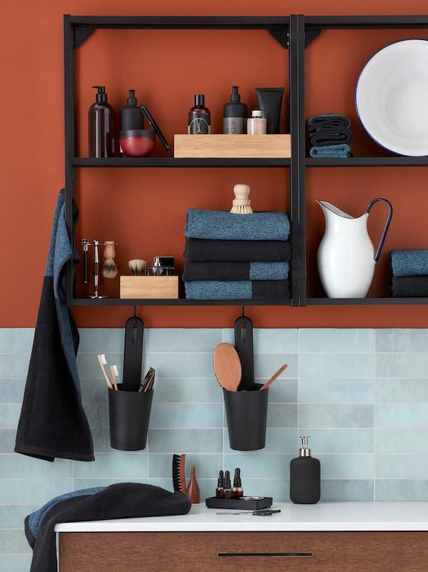 Bagno con piastrelle grigio-blu e pareti rosse con una strutture da parete con ripiani ENHET su cui sono riposti asciugamani piegati e prodotti per il bagno - IKEA