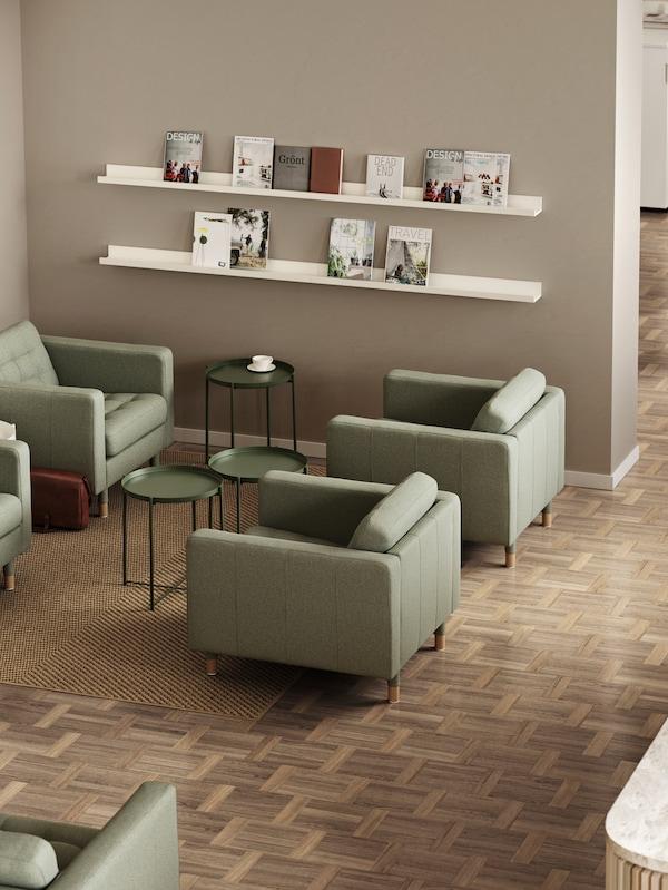 Quattro poltrone LANDSKRONA verdi con tavolini vassoi GLADOM e, sulla parete, delle mensole per quadri con esposte alcune riviste.