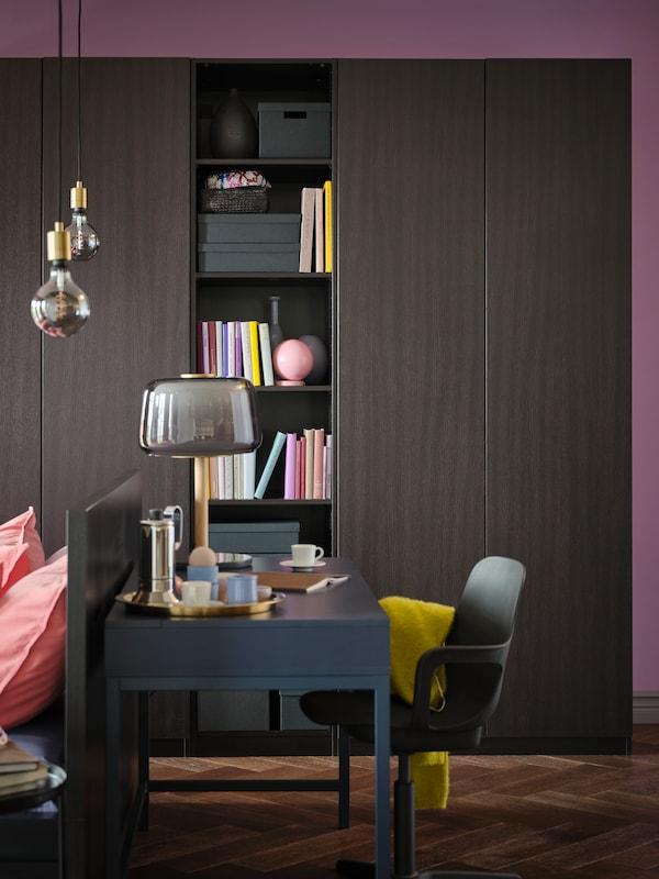 Alex íróasztal és egy ODGER szék áll egy fekete-barna PAX/FORSAND gardrób előtt, a polcok könyveket és dobozokat tartanak.