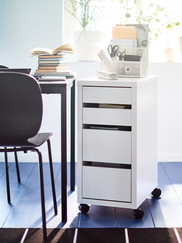 En hvit MICKE skuffeseksjon på hjul med hvit oppbevaring til skrivebord på, står ved siden av et svart bord.