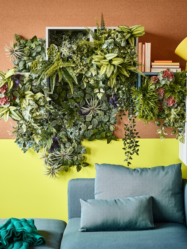 A living room with FEJKA artificial potted plant fern in plastic, above a sofa on a wall with fake plants.