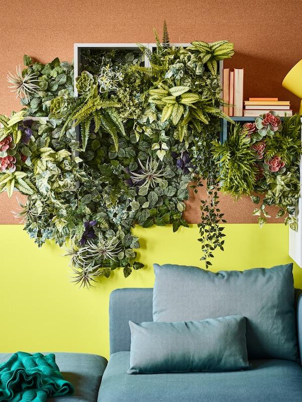 Unha sala de estar cunha planta artificial FEJKA en testo, sobre un sofá nunha parede con outras plantas artificiais.