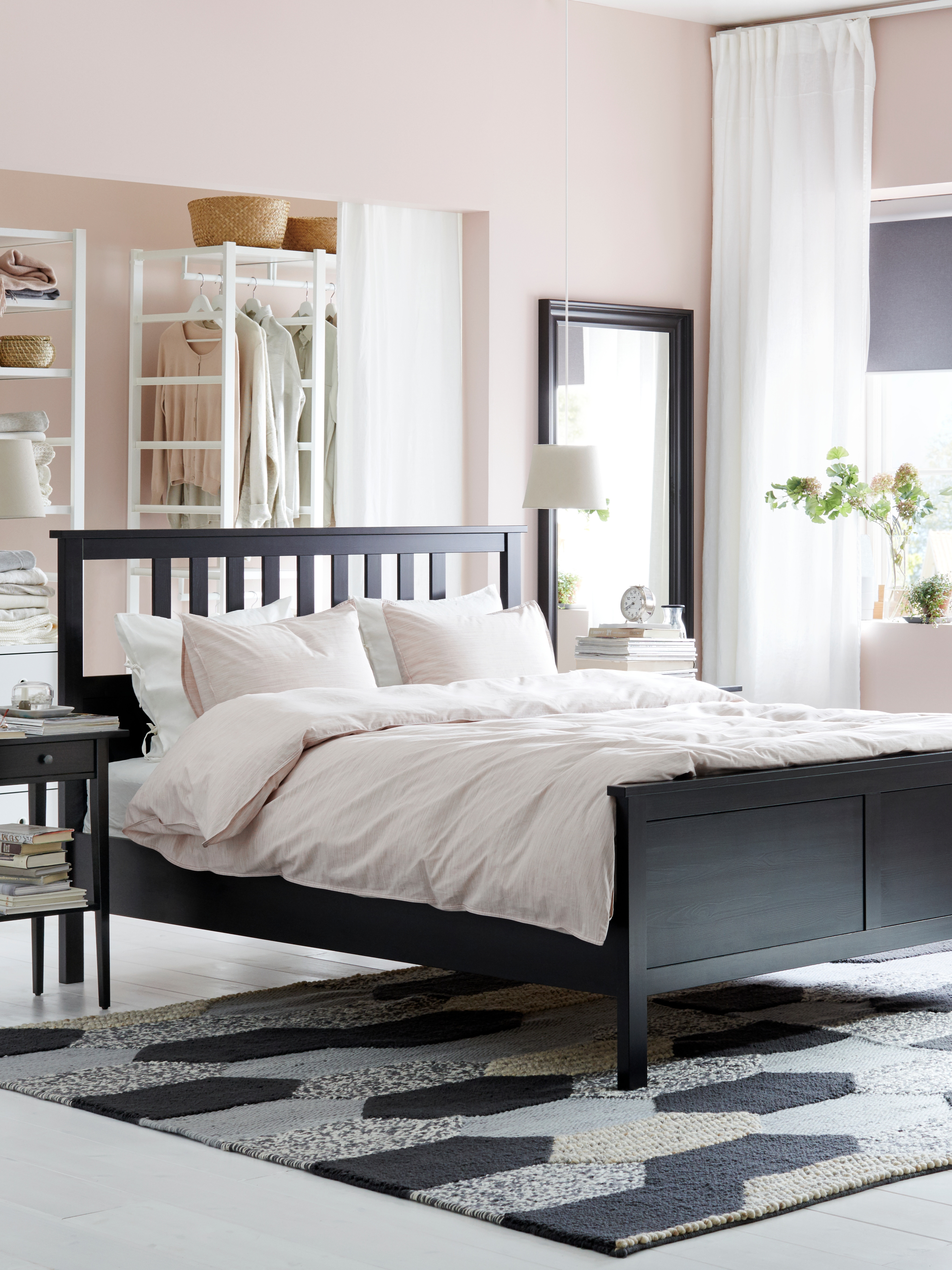 A black-brown HEMNES bed frame with a pink quilt cover in is in the middle of a bedroom by a matching bedside table.