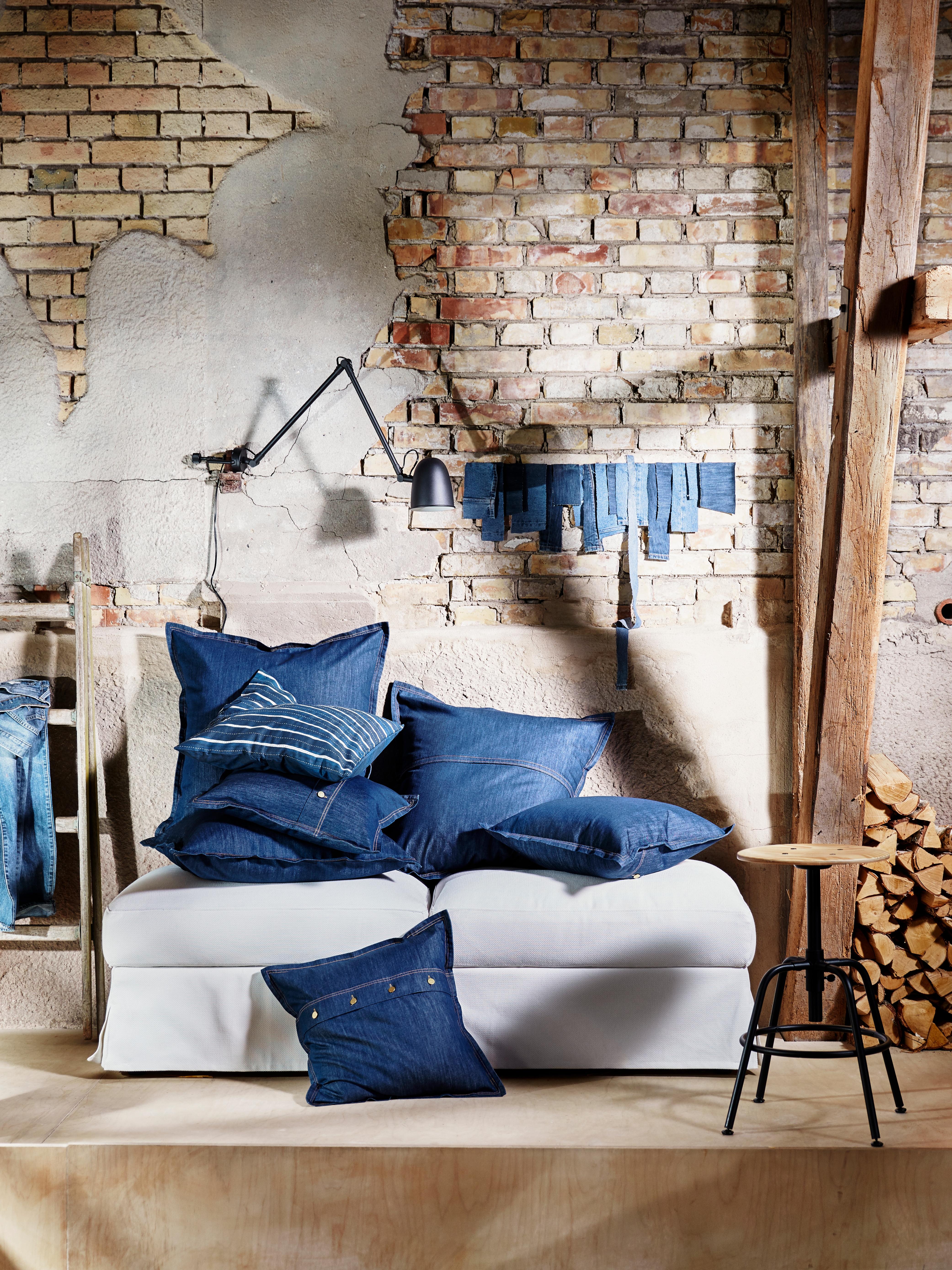 Sofa ispunjena SISSIL ukrasnim jastučnicama i tkaninom od obojenog plavog trapera, ispred visokog zida od opeke s deblima.