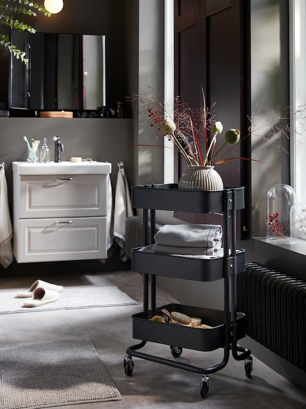 A black RÅSKOG trolley on castors with decorative flowers, hair accessories and folded grey towels on the shelves.