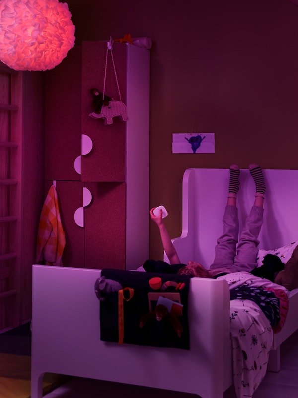 Une enfant couchée sur le dos dans son lit utilise une télécommande STRYBAR pour changer la couleur de l'ampoule à DEL de sa suspension VINDKAST.