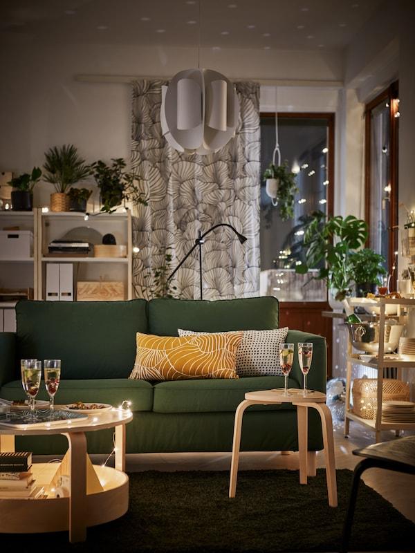 A berendezett nappaliban egy kétszemélyes sötét zöld PÄRUP kanapét látunk díszpárnákkal. Mellette dohányzóasztal áll pezsgős poharakkal.