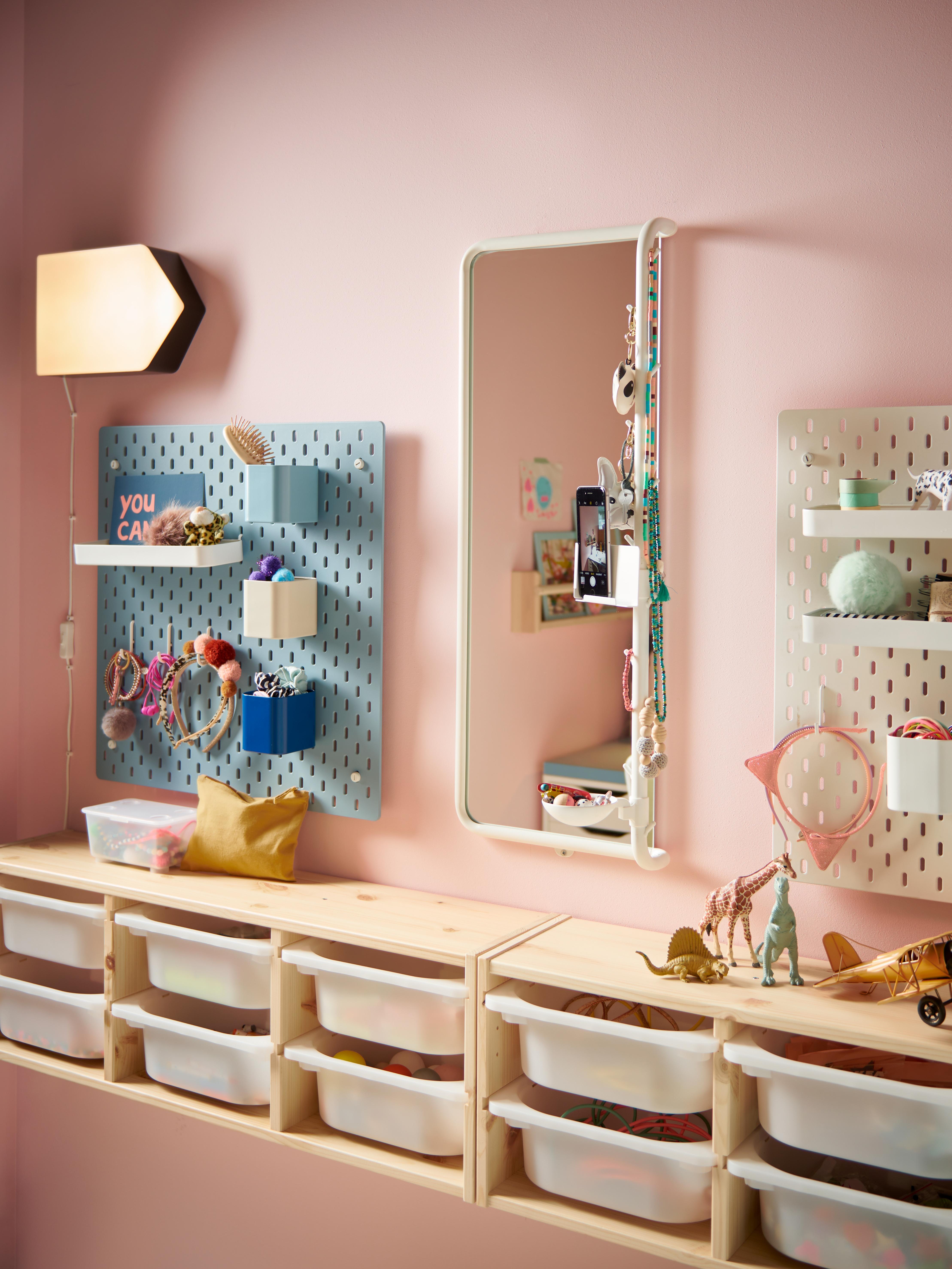 Dětský pokoj s dvěma dírkovanými deskami na stěně, velkým zrcadlem uprostřed. Dole jsou úložné díly TROFAST.