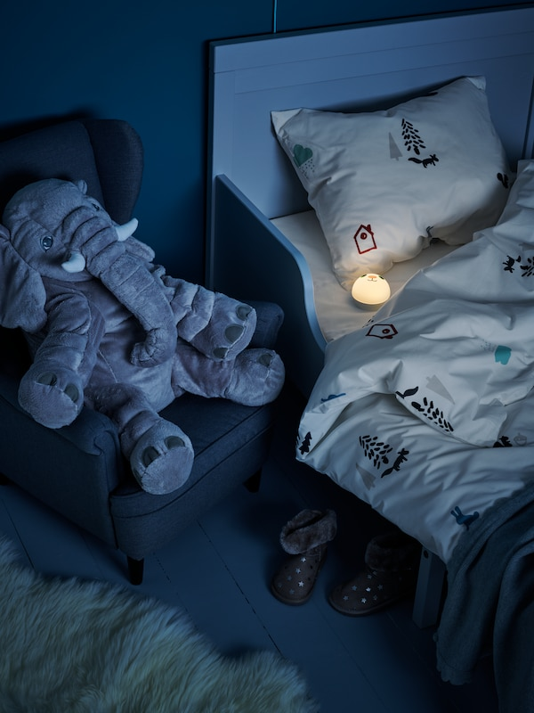 A JÄTTESTOR soft toy elephant seated in a children's armchair next to a bed where a lit KORNSNÖ LED night light lies.