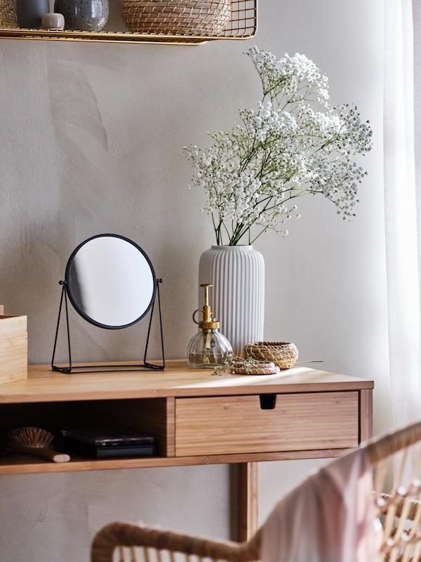 طاولة زينة  NORDKISA من الخيزرانبمحاذاة الحائط، مع مرآة طاولة LASSBYN،وفوقها مزهرية STILREN بيضاء.
