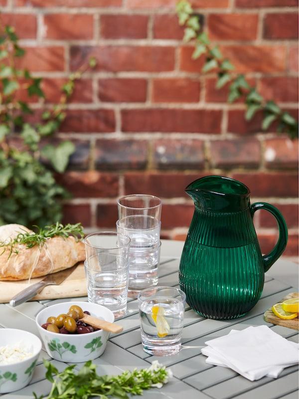 Na záhradnom stole BONDHOLMEN je prestreté na obed. Je na ňom džbán SÄLLSKAPLIG, miska STILENLIG solivami, poháre GODIS aďalšie predmety.