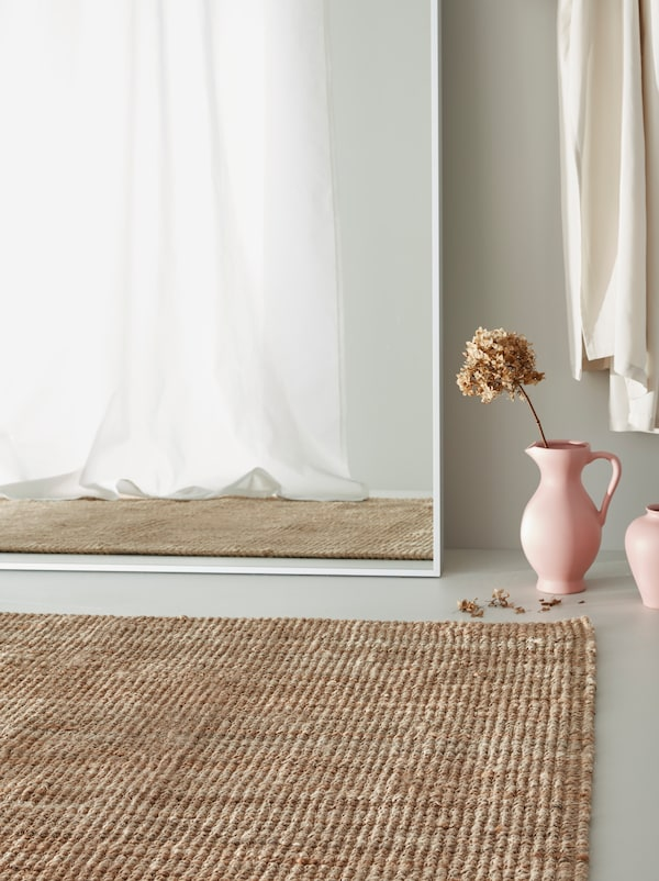 A HOVET mirror leans against a wall next to a LOHALS jute rug and two pink vases.