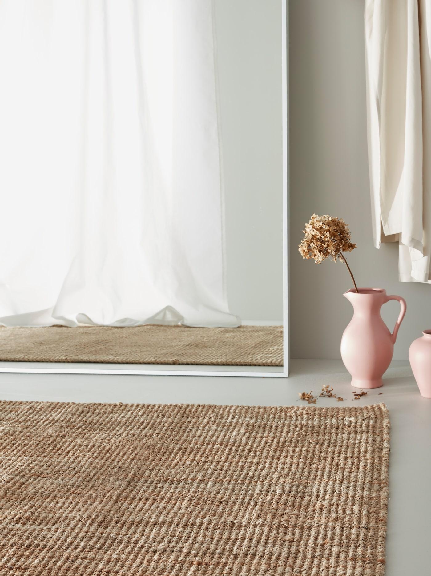 У стены стоит зеркало ГУВЕТ, рядом лежит джутовый ковер ЛОХАЛЬС и стоят две розовые вазы.