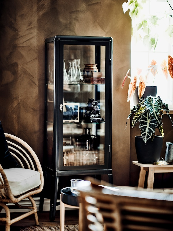 A glass-door cabinet with decorative items stored inside, a green plant and a rattan armchair with a white cushion.