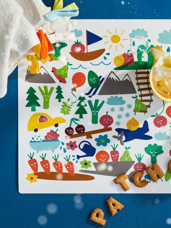 Salpicones de leche de un tazón sobre un mantel individual MATVRÅ de colores; encima hay varias galletas y toallas KRAMA.