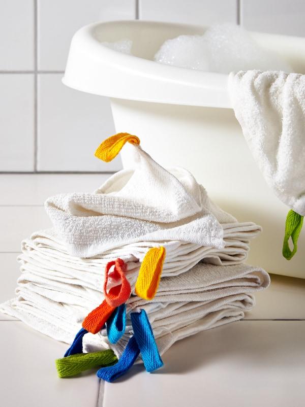 Morea de panos KRAMA pousados no chan diante dunha bañeira infantil LÄTTSAM. Un pano colgado da bañeira.