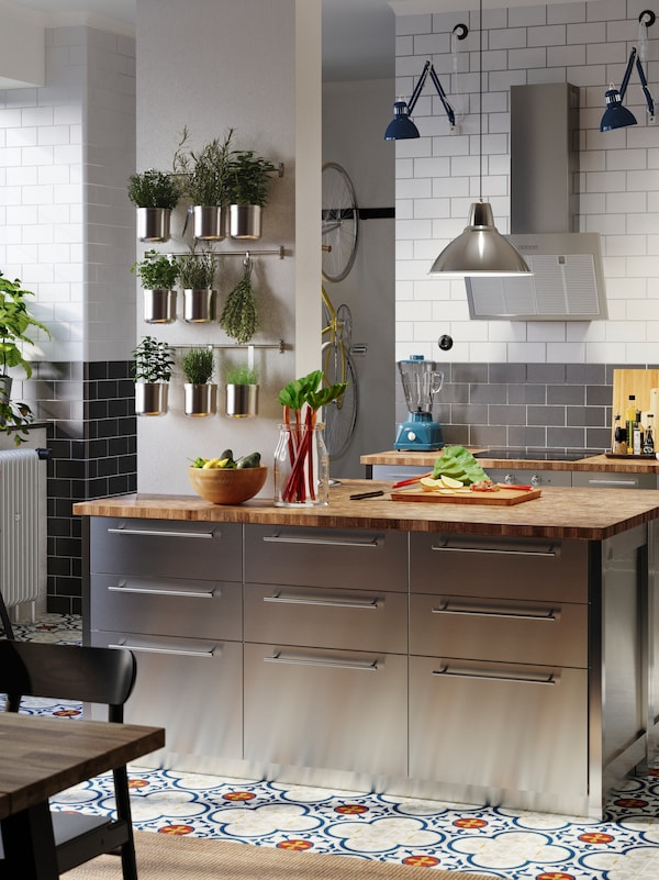 O insulă de bucătărie din inox, podele cu mozaic, tocător pe un blat din lemn și plante aromatice prezentate pe perete.