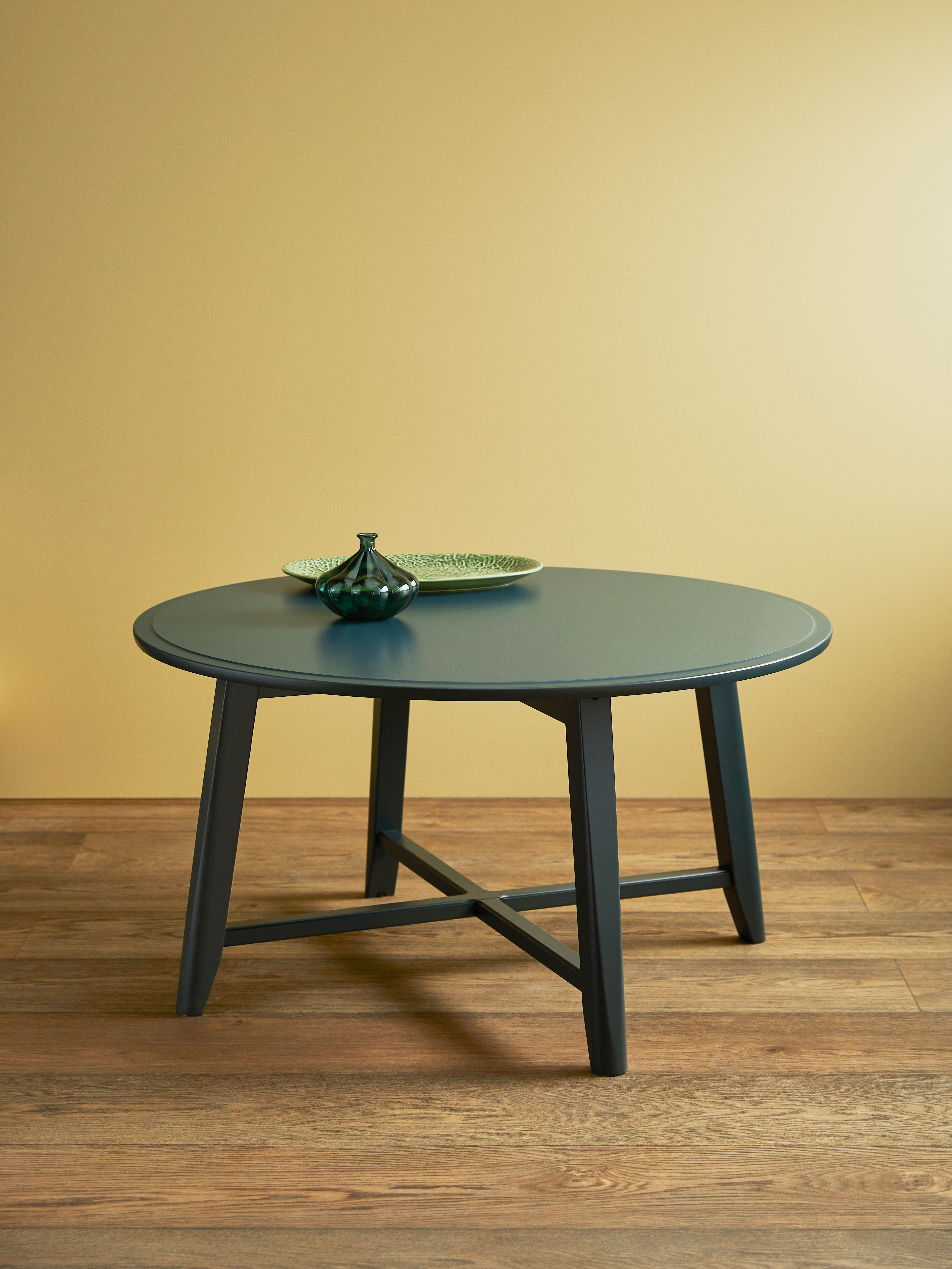 A round, dark blue-green KRAGSTA coffee table stands on a wooden floor by a yellow wall. A green vase and plate sit on top.