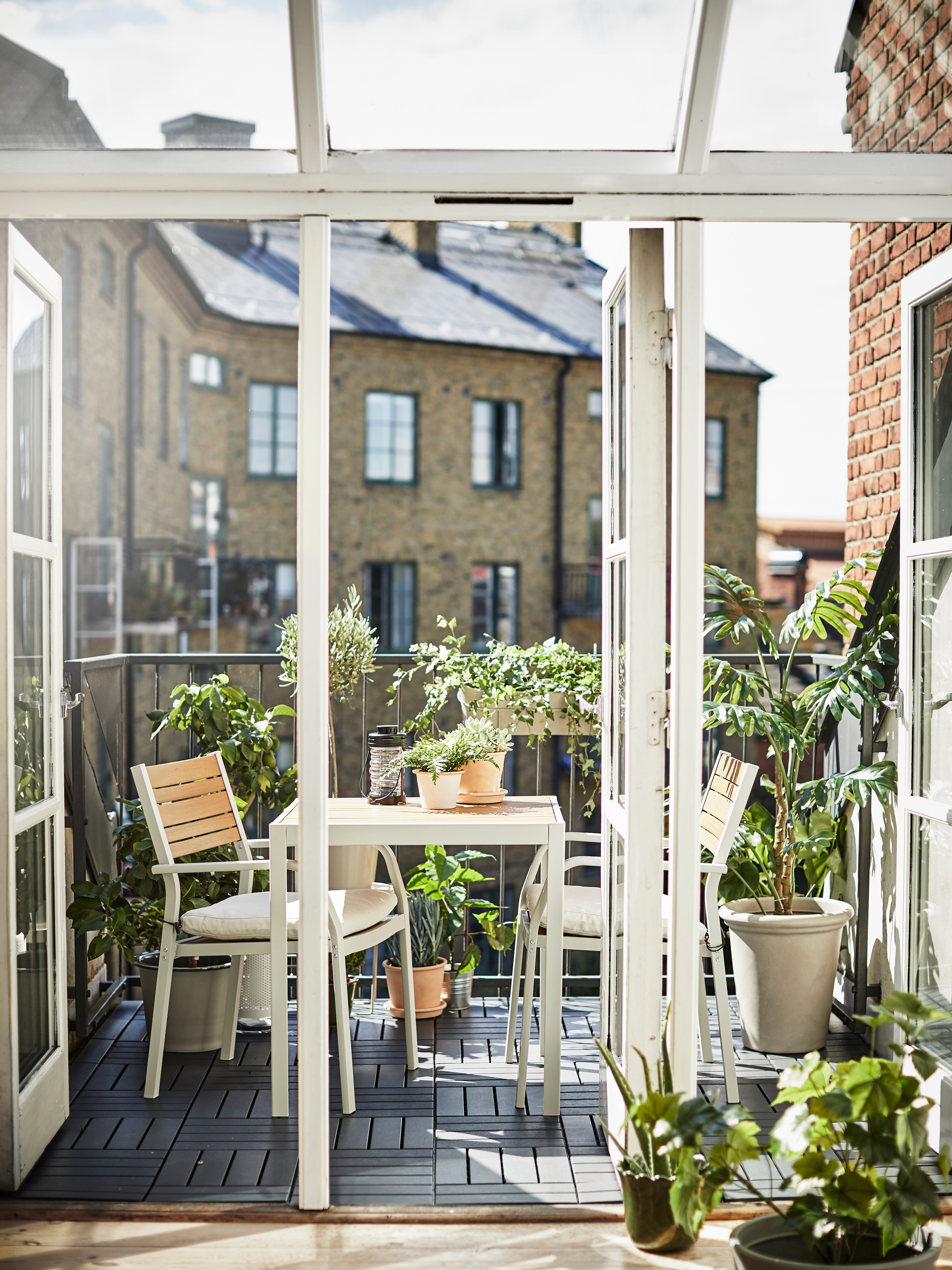 Open balcony with multiple plants, CHILIPEPPAR and MUSKTOBLOMMA plant pots, two white chairs, and a white MELLTORP table.