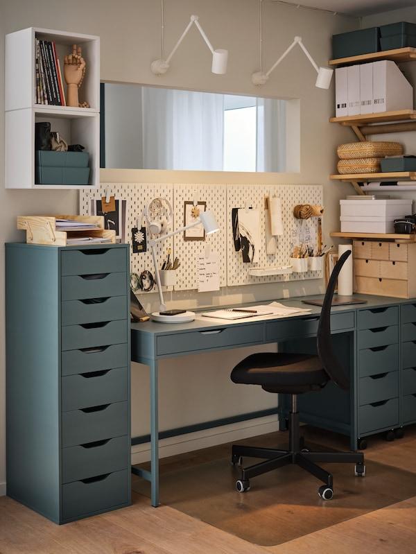 Sivo-tirkizni ladičari i radni stol, crna uredska stolica, bijela rupičasta ploča, police s nosačima.