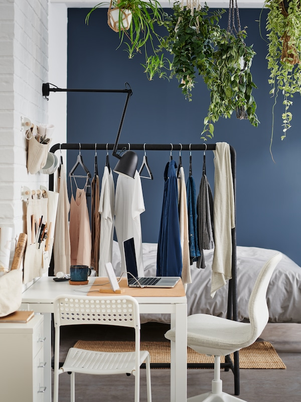 A white MELLTORP table with a white ADDE chair and beige LÅNGFJÄLL office chair, beside a black TURBO clothes rack and a bed.