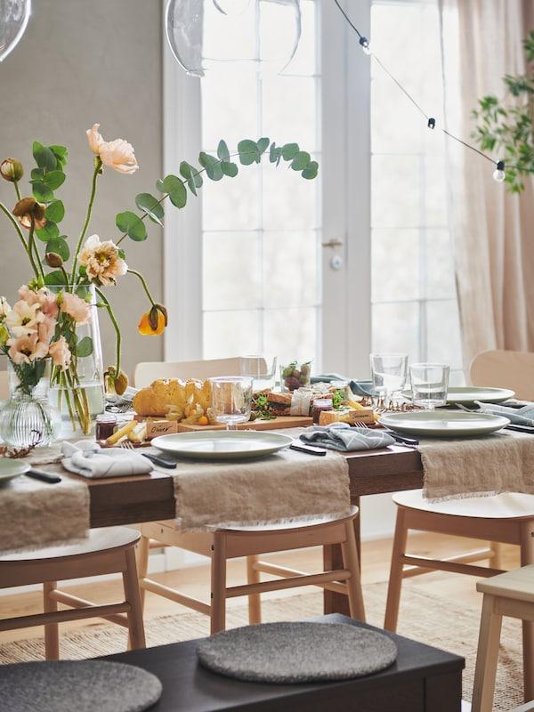 โต๊ะ MÖRBYLÅNGA/เมอร์บีลองงา ที่จัดไว้สำหรับงานเลี้ยงพร้อมด้วยผ้าเมตร AINA/อัยน่า สีเนเชอรัล, จาน FÄRGKLAR/แฟรีคลาร์, ดอกไม้ในแจกัน และของตกแต่งหลายอย่าง