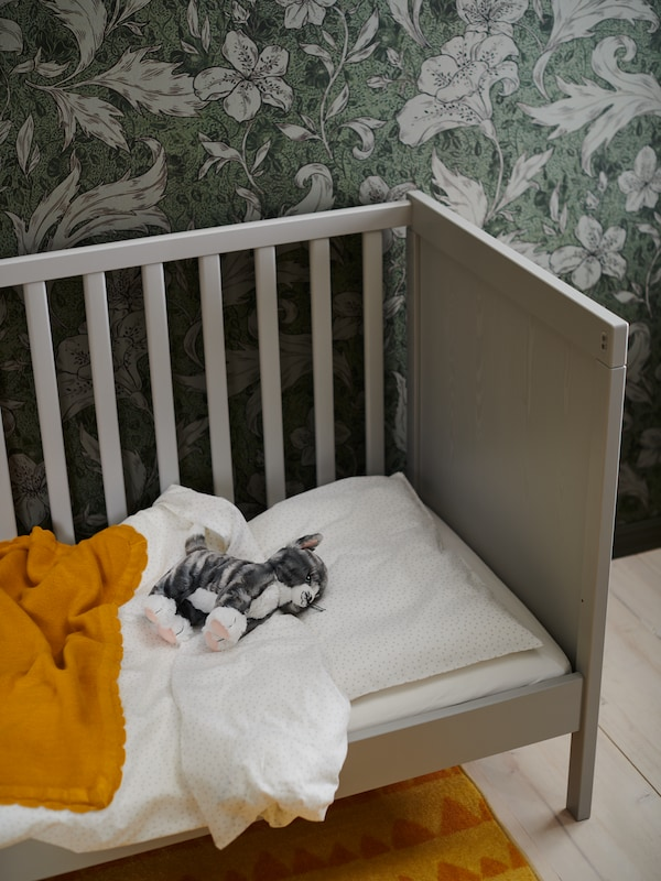 A crib with white and orange blankets, a cat soft toy and flowery wallpaper.