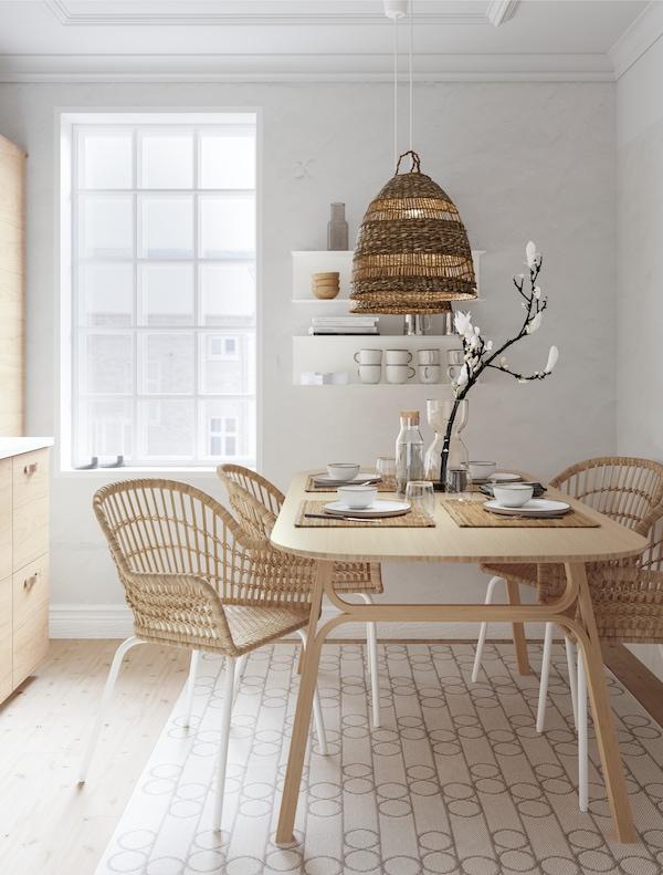 Une salle à manger minimaliste dans des tons naturels avec une table en bambou, des chaises en osier et un meuble de rangement en bois sur le mur.