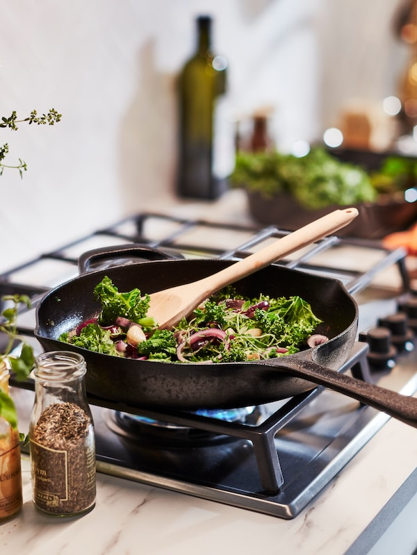 A VARDAGEN cast iron frying pan stands on a gas stove with vegetables and a wooden spoon inside.