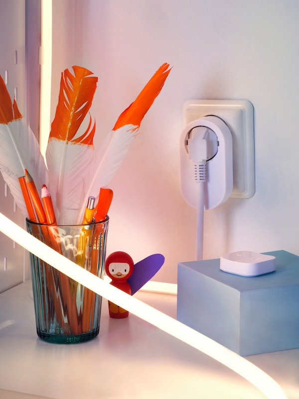 The corner of a small desk with a TRÅDFRI control outlet kit, a LED lighting strip and a glass holding pencils and feathers.