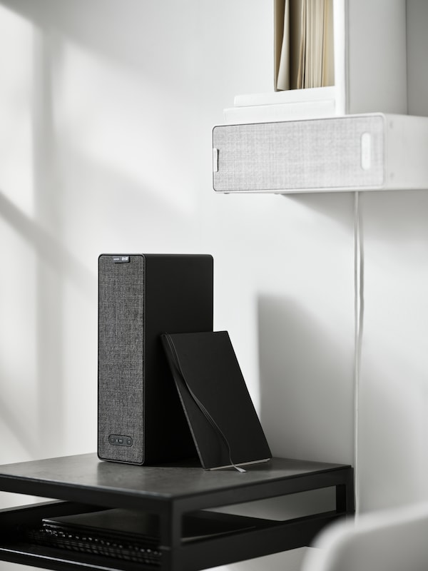 Two SYMFONISK WiFi bookshelf speakers, the white one is on the wall with books on it, the black one is on a black side table.