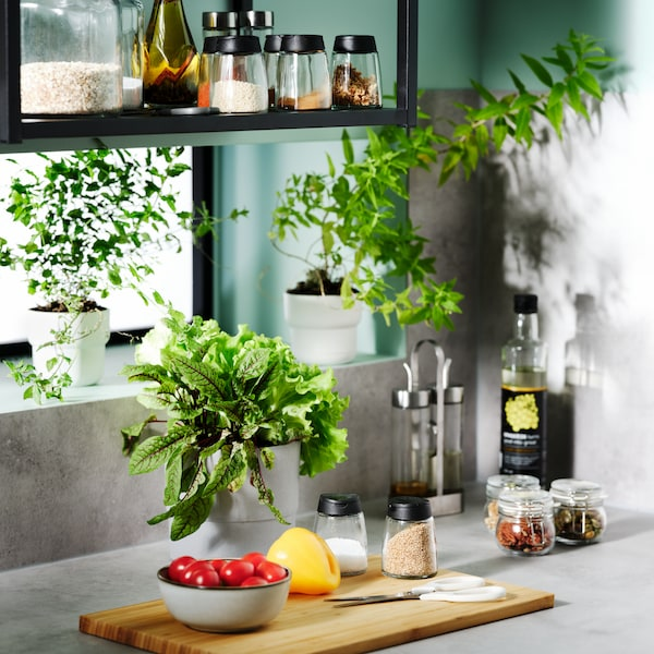 Un comptoir de cuisine avec une planche à découper en bois sur le dessus, un bol de tomates, un poivron jaune et des pots à épices.