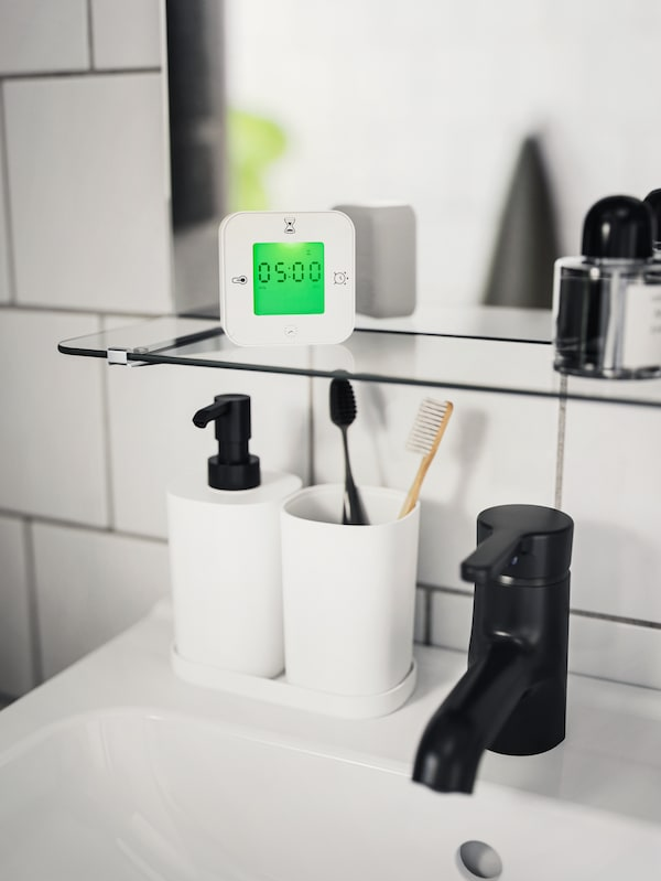White KLOCKIS clock/timer set on a glass shelf above a NYSJÖN/BJÖRKÅN wash basin cabinet with STORAVAN 3 piece bathroom set.