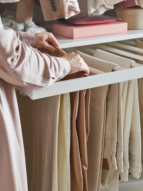 Eine KOMPLEMENT Hosenaufhängung ist hier mit aufgehängten Hosen zu sehen.