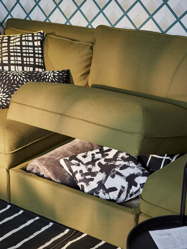 A VALLENTUNA green modular sofa unit with storage compartment propped open, black and white patterned pillows under.