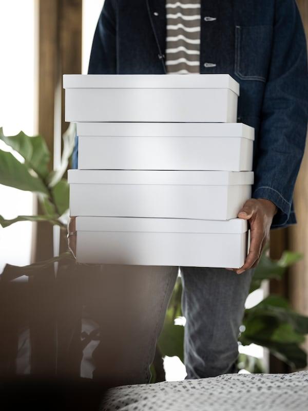 Person håller i TJENA lådor.
