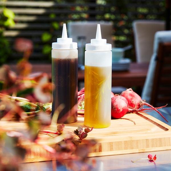 Deux bouteilles de condiments posées sur une planche à découper APTITLIG en bambou.