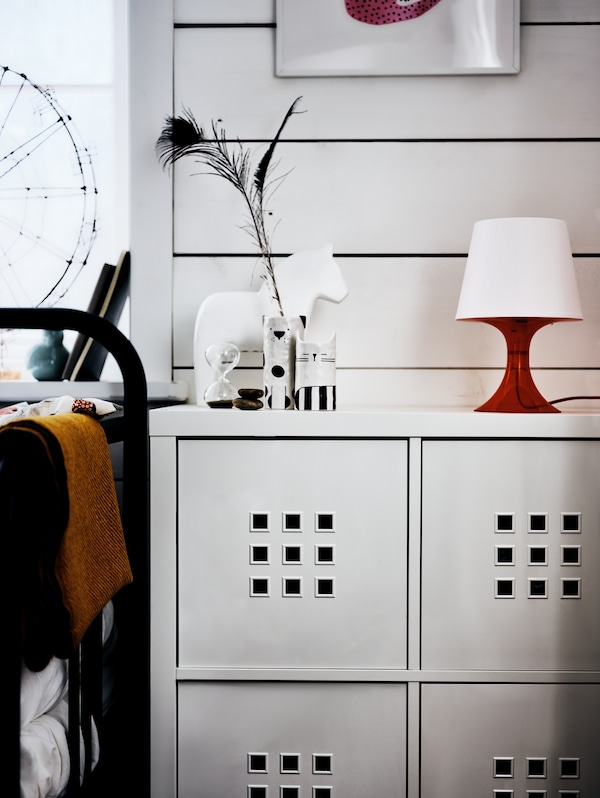 A KALLAX shelving unit with a red lamp, a white model horse and a vase on it, beside a bed frame, in front of a white wall.