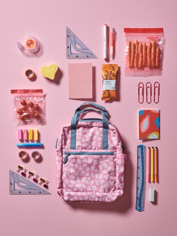 На розовом полу лежит рюкзак с рисунком в розовой гамме, вокруг разложены школьные принадлежности: ручки и скрепки.