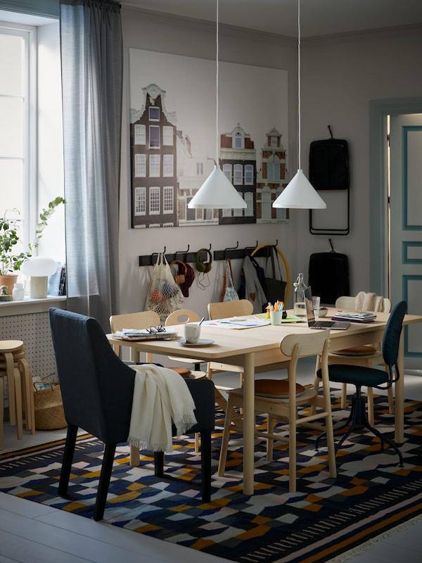 Une salle à manger avec une table et des chaises RÖNNINGE en bouleau sur un tapis TÅRBÄK multicolore, et au-dessus, des suspensions NÄVLINGE blanches.