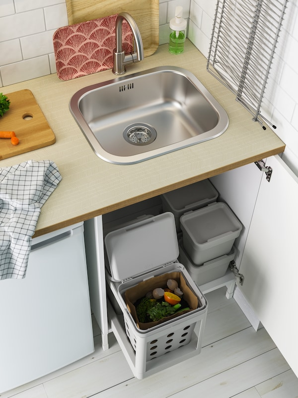 A door under the sink is open, revealing light grey waste sorting baskets that slide out and small stacked baskets.