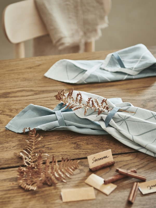 A wooden tabletop being prepped for a party, with decorations, handwritten name signs and folded, blue SANDVIVA tea towels.
