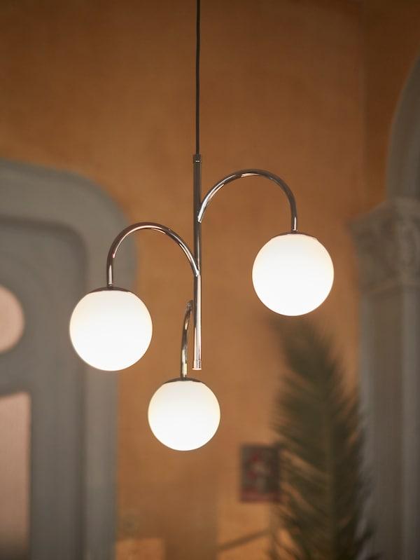 Eine Deckenleuchte mit drei Leuchtmitteln hängt in einem Wohnbereich mit einer Zimmerpflanze von der Decke.