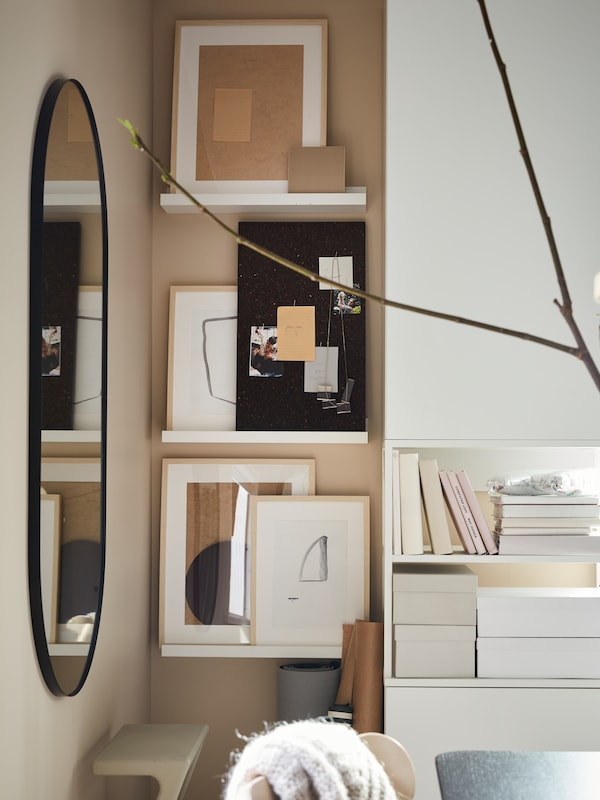 A corner of a bedroom with a mirror and white picture ledges with a SVENSÅS memo board and picture frames with works of art.