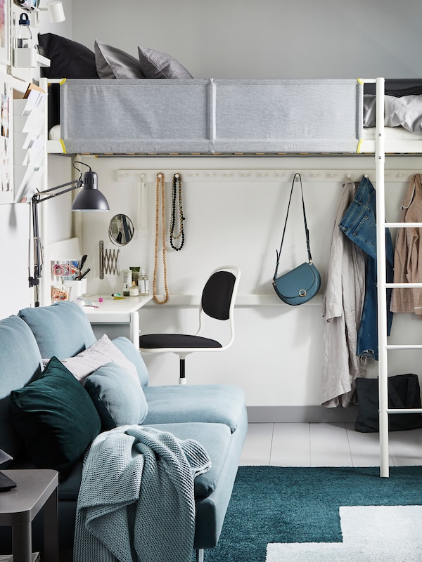 A white VITVAL loft bed with a grey fabric guard rail and a desk underneath with bags and clothes hanging on hooks.