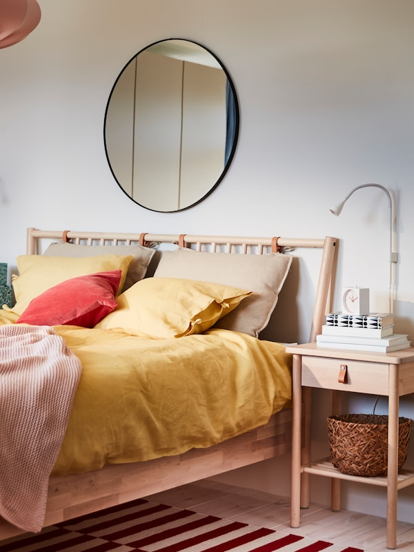 A BJÖRKSNÄS bedside table and bed with yellow PUDERVIVA bed linen and INGABRITTA throw, and a mirror on the wall behind.
