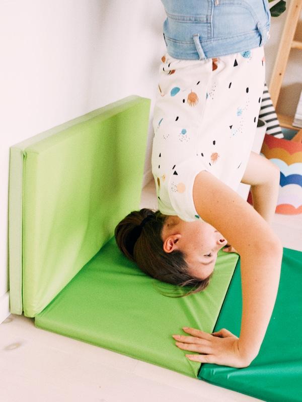 Una ragazza fa la verticale contro il muro, appoggiando testa e mani a un tappetino da ginnastica pieghevole PLUFSIG verde brillante.