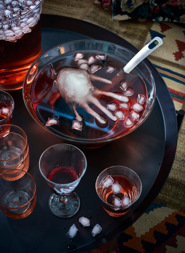 A punch bowl with red punch filled with ice cubes and one human hand shaped ice cube, sitting on a black table with glasses.