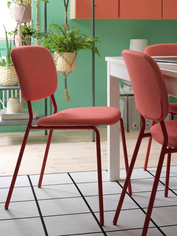 Une salle à manger avec un gros plan sur des chaises rouges, une table blanche et un tapis à motifs carrés noir et blanc.